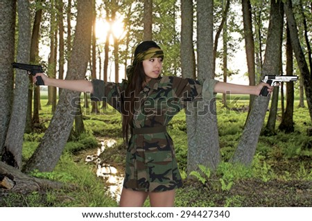Beautiful young Asian woman soldier with a gun - stock photo