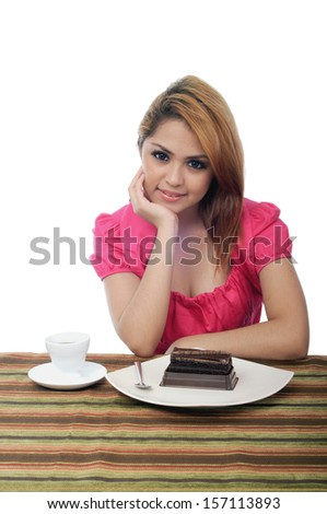 Beautiful young asian woman staring with hand on cheek and elbow on table isolated on white background