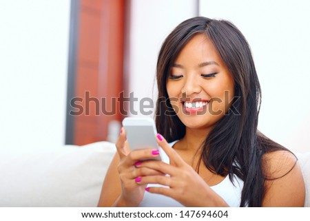 Beautiful young asian woman text messaging with her smart phone at home - stock photo