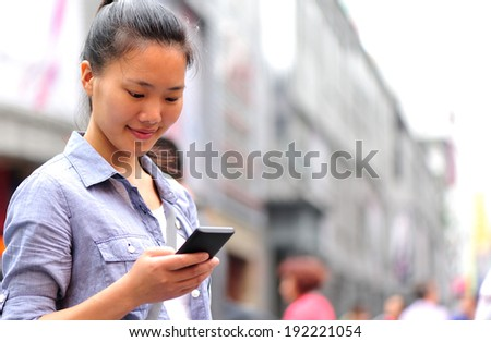 beautiful young asian woman using smart phone on shopping street  - stock photo