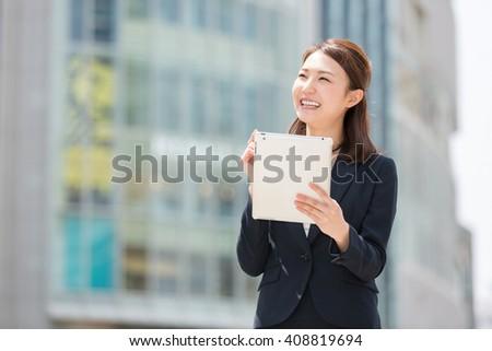 Beautiful young asian woman using tablet computer - stock photo