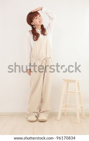 Beautiful young Asian woman wearing overalls in a bright room - stock photo