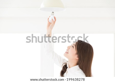 Beautiful young asian woman who exchanges a LED electric bulb - stock photo