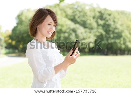 Beautiful young asian woman who see a smart phone - stock photo