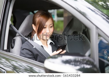 Beautiful young asian woman who see a smart phone in a car