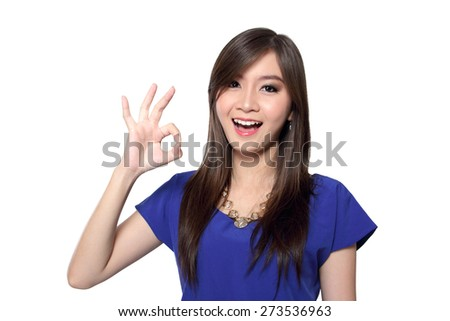 Beautiful young Asian woman with big bright smile making okay hand gesture while looking at camera, isolated on white background