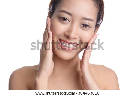 Beautiful young asian woman with clean fresh skin, hand touching face, isolated on white background - stock photo
