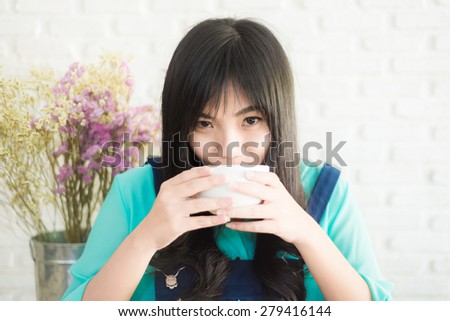 Beautiful young Asian woman with cup of coffee while relaxing at home. White brick wall - stock photo