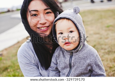 Beautiful young asian woman with freckles and her son relaxing outdoors. Mother brunette with dark hair holds her blond son in bear hood. Unusual appearance, diversity and heredity concept - stock photo