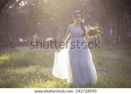 Beautiful young asian woman with long curly hair walking with bouquet roses in a garden. with vintage toned style and lighting of sun as background.