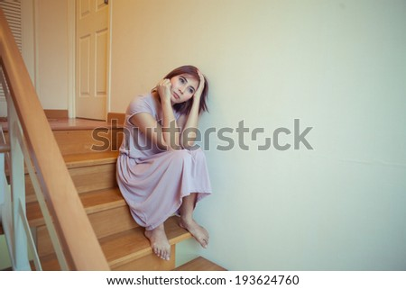Beautiful young asian womanl sits alone on stairs in house - stock photo