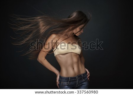 beautiful young athletic brunette woman with long straight flying hair isolated on dark background