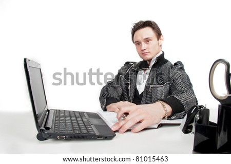 beautiful young attractive caucasian businessman in fashionable clothes sitting in office of the table in front of a laptop,working,thinking,isolated over white,working process in office,employee