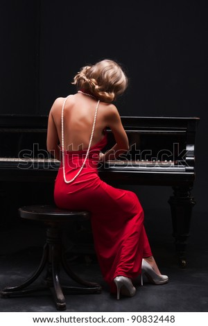beautiful young attractive woman in evening dress and piano