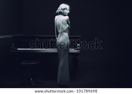 beautiful young attractive woman in evening dress and piano (black and white shoot)