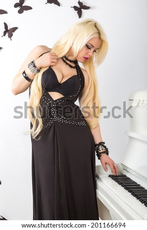 beautiful young attractive woman in evening dress and piano in a light room - stock photo