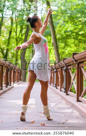 Beautiful young ballerina dancing, posing and standing on tiptoes. Outdoors, spring