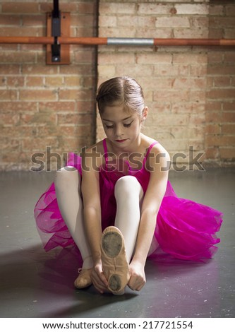 Beautiful young ballerina getting ready for class - stock photo