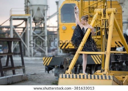 Beautiful young ballerina posing on a ladle of a hoisting machinery which is behind her. She is wearing black tutu and ballet shoes. She is holding her outstreched leg with her hand. There are