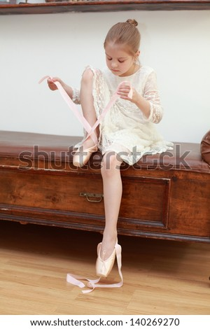 Beautiful young ballet dancer in a white dress sits on a chair and puts on pointe