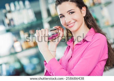 Beautiful young barista preparing a cocktail with a shaker and smiling at camera
