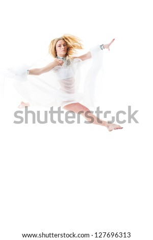Beautiful young belly dancer jumping, modern ballet. Girl dancing in white cloth. Beautiful young belly dancer, modern ballet. young and beautiful dancer posing on studio background.