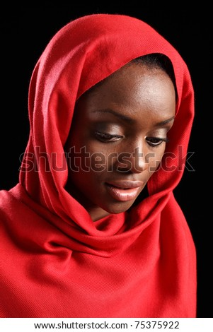 Beautiful young black african american muslim girl wearing red hijab, eyes looking downwards taken against a black background. - stock photo