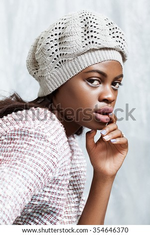 Beautiful young black ethnicity girl in hat posing in the studio, wearing fashion clothes.