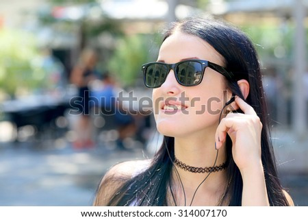 beautiful young black hair woman listening music with earphones in the city - stock photo