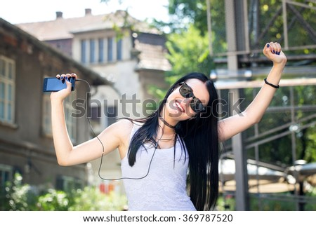beautiful young black hair woman with sunglasses listening music with earphones in the city - stock photo