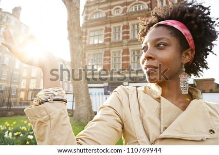 Beautiful young black woman holding the sun between her fingers at sunset while visiting London city. - stock photo