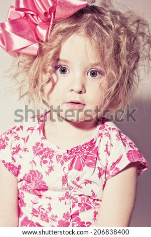 Beautiful young blond female child with curly hair posing in studio - stock photo
