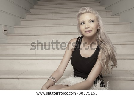 Beautiful young blond female sitting on stairs