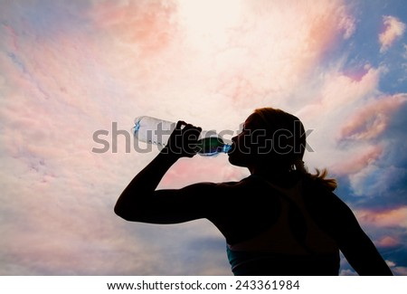 Beautiful young blond girl drinking water in the evening (sunset) - stock photo