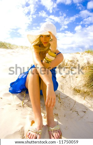 beautiful young blond girl sitting on the beach in a blue dress