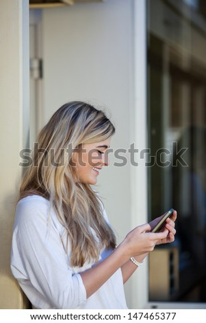 Beautiful young blond girl student sending an sms on a mobile phone while leaning against the exterior wall of a building
