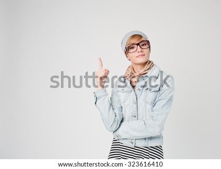 Beautiful young blond hair woman in glasses and hat  with finger point up. Hipster young and beautiful