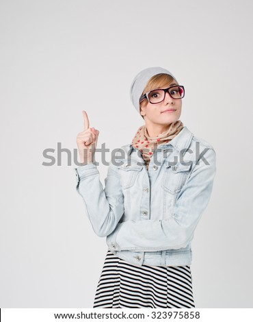 Beautiful young blond hair woman in glasses and hat  with finger point up. Hipster young and beautiful - stock photo