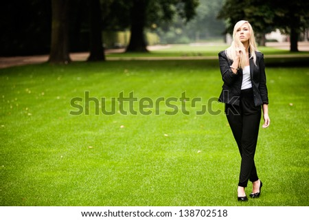Beautiful young blond standing on the grass in the park in formal uniform - stock photo