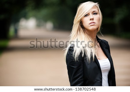 Beautiful young blond standing outdoor in formal uniform - stock photo