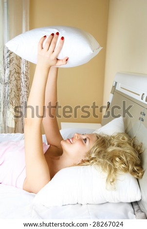 beautiful young blond woman at home in bed bed with a pillow in her hands