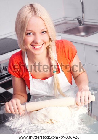 beautiful young blond woman baking in the kitchen at home - stock photo