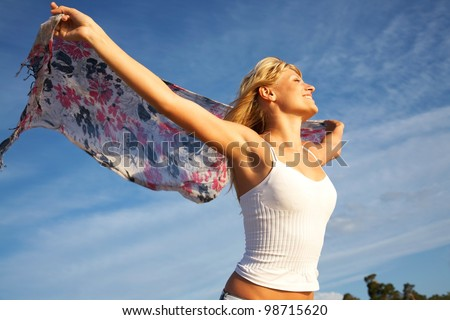 beautiful young blond woman dancing with kerchief against the blue sky - stock photo