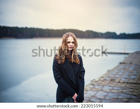 beautiful young blond woman in a black jacket on a cold pier at the lake in winter
