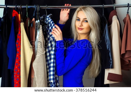 beautiful young blond woman in a clothing store. Happy young lady with a lot of clothes. Shopping concept.
