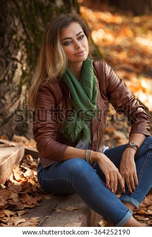 Beautiful young blond woman in a park relaxing - stock photo