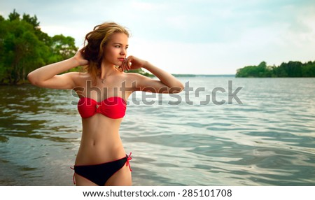 beautiful young blond woman in a swimsuit on the beach resting enjoying the evening sun and good weather - stock photo
