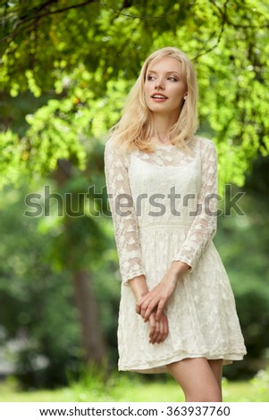 Beautiful young blond woman in a white dress outdoors  - stock photo