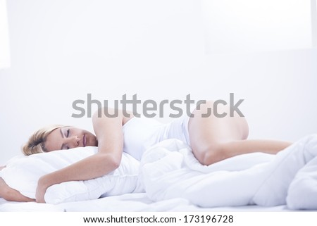 Beautiful young blond woman in bed - stock photo