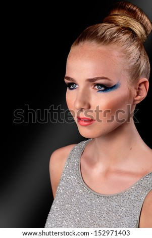 Beautiful young blond woman in creative fashion makeup with a serious pensive expression staring straight ahead on a dark background